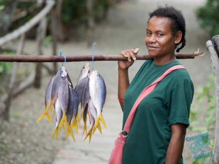 Lady carries fish on a stick